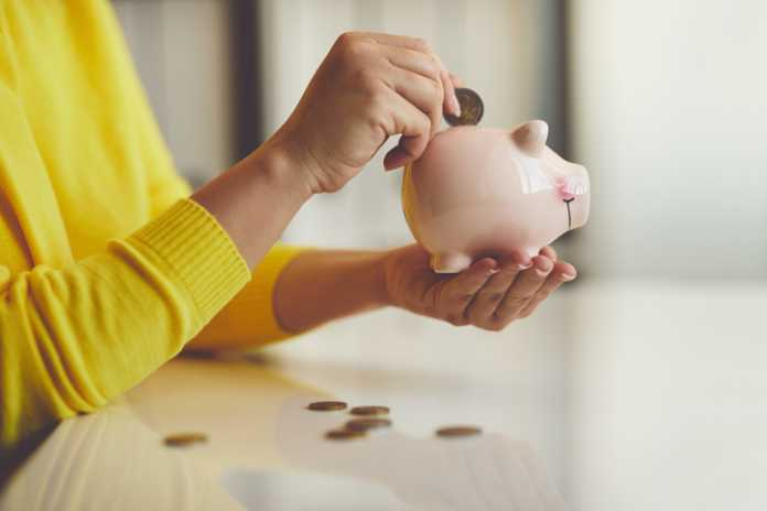 Close up of woman puts euro coin into piggy bank